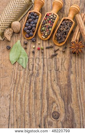 Various spices in wooden scoops on a wooden background