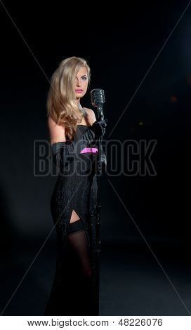 Portrait Of A Beautiful Blonde Woman In Black Dress And Gloves With A Retro Microphone