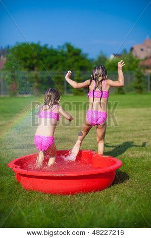 Two Little Sisters Frolicing And Splashing In Their Yard In Small Pool