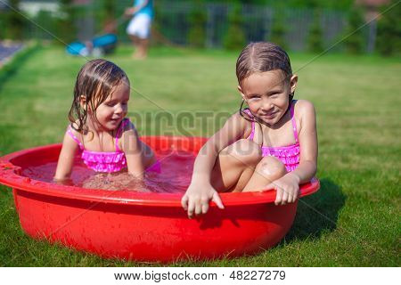 Two Cute Little Sisters Frolicing And Splashing In Their Yard In Small Pool