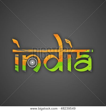 text India in tricolors with Ashoka Wheel on abstract grey background.