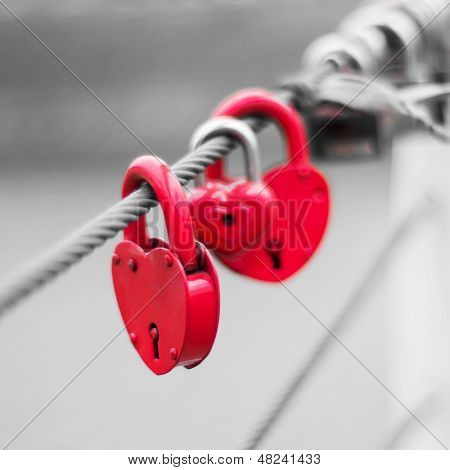 Red Locks in hart shape on rope bridge