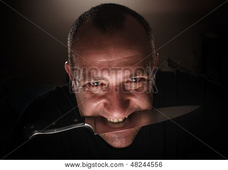 Dramatic portrait of angry sinister man gripping knife between teeth, closeup.