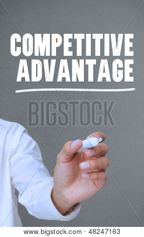 Hand writing competitive advantage with a marker on grey background