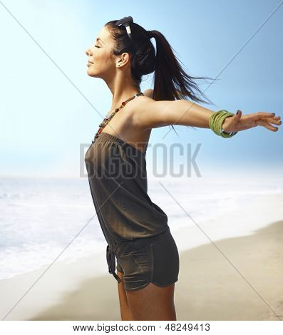 Pretty girl enjoying summer sun and fresh air and wind on the beach eyes closed, arms wide open Side view.