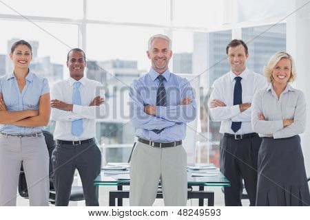 Team of smiling business people standing with arms folded in the boardroom