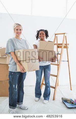 Pretty young housemates carrying moving boxes and smiling at camera in their new home