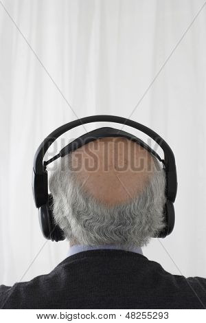 Rear view of a senior man wearing headphones against white background
