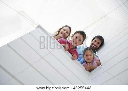Low angle view of happy parents with children looking over white wall