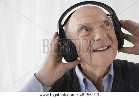 Closeup of a senior businessman wearing headphones against white background