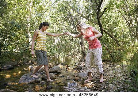 Dos adolescentes sosteniendo las manos y cruce arroyo en el bosque