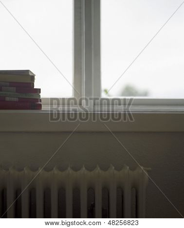 Closeup of cropped stack of books on windowsill