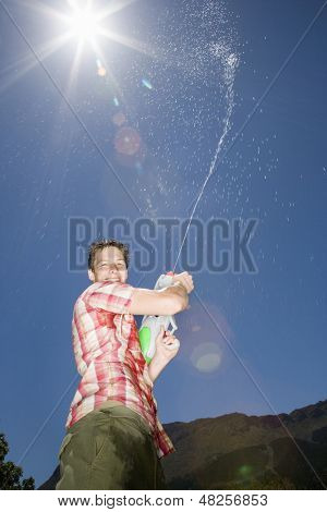 Portrait of teenage boy spraying water from gun into air