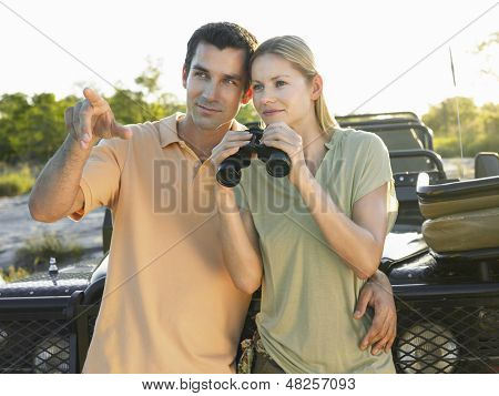Yung couple standing against jeep with binoculars