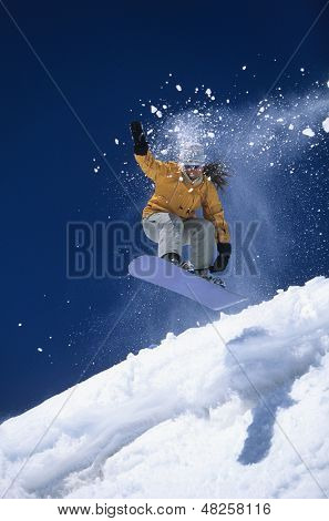 Low angle view of a snowboarder in midair above ski slope with snow powder trailing behind