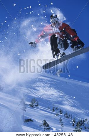 Low angle view of a snowboarder in midair with snow powder trailing behind above ski slope