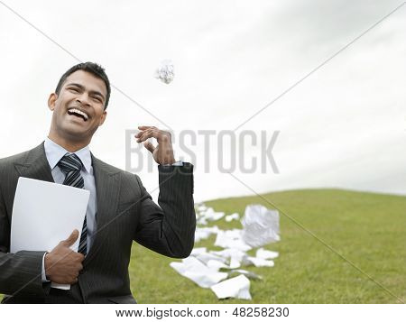 Laughing young businessman on grass field throwing litter behind