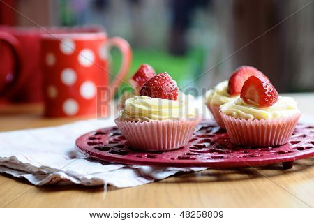 Strawberry And Vanilla Cupcakes On Kitchen Table