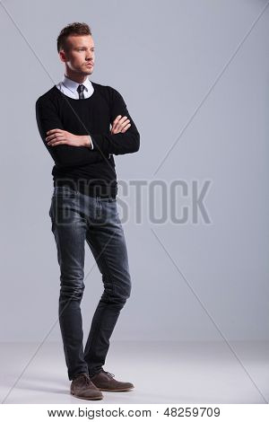 full length picture of a casual young man standing with his hands crossed and looking away from the camera. on gray studio background
