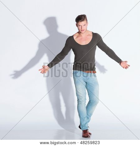 full body picture of a casual young man extending his arms while looking at the camera with rage. on gray studio background with shadow