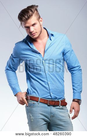 young casual  man looking at the camera while holding his hand on his belt. on gray studio background