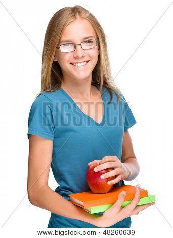 Chica joven estudiante flaco tiene libros de ejercicios y apple, aislado en blanco