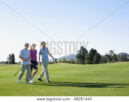 Three young golfers walking on golf course