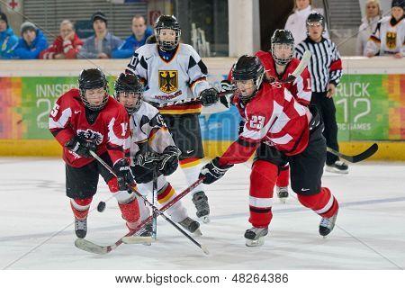 INNSBRUCK, AUSTRIA - JANUARY 20 Katharina Oertel (Germany) and Anja List Polczik (Austria) fight for the puck in the ice hockey tournament on January 20, 2012 in Innsbruck, Austria.