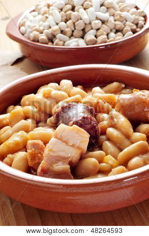 closeup of an earthenware bowl with fabada asturiana, a typical spanish bean stew
