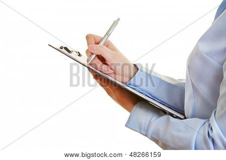 Hand holding pen and checklist on a clipboard