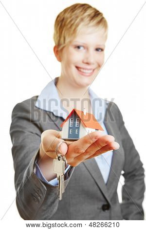 Smiling property broker with a small house and keys
