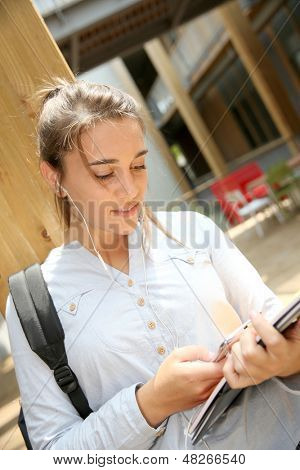 Teenage girl using smarphone at school