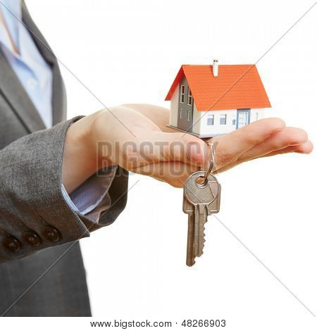 Hand of a woman holding little house and keys