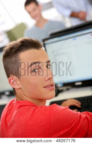 High-shool boy sitting in front of desktop computer