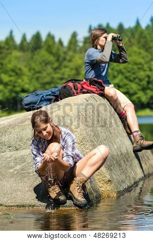 Teenagers resting and birdwatching by lake young hikers sporty