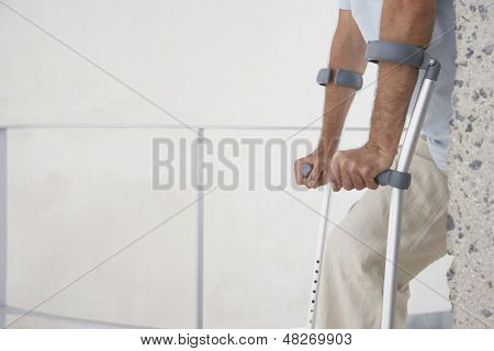 Midsection of man walking with crutches at home