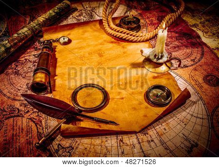 Vintage compass, magnifying glass, pocket watch, quill pen, spyglass lie on an old ancient map with a lit candle. Vintage still life.