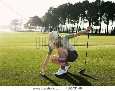 Full length of young female golfer placing ball on tee