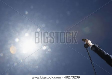 Businessman's hand holding telephone receiver against sky