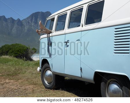 Woman's feet sticking out of campervan window with mountains in background