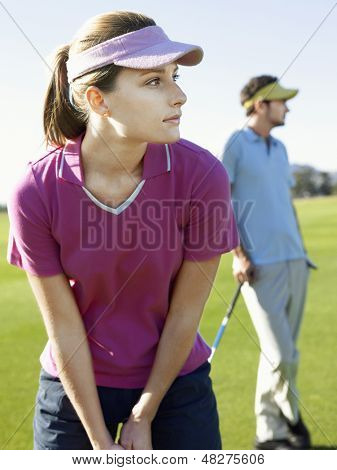 Young woman playing golf with male friend on golfcourse