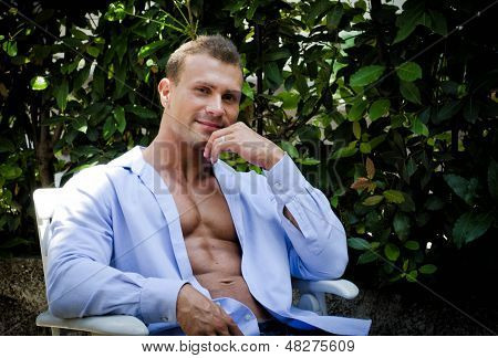 Handsome Young Muscle Man Smiling, Outdoors, Sitting With Open Shirt