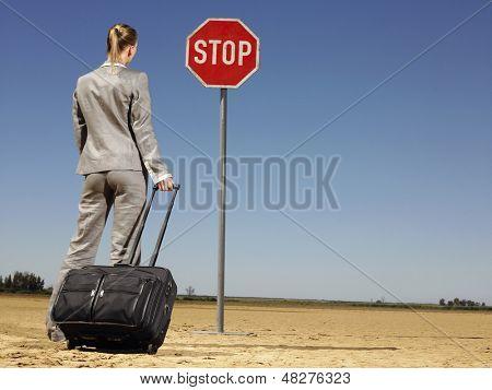 Rückansicht des jungen geschäftsfrau mit Gepäck am Stop-Schild auf Wüste suchen