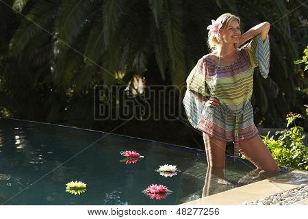 Beautiful young woman standing in outdoor swimming pool
