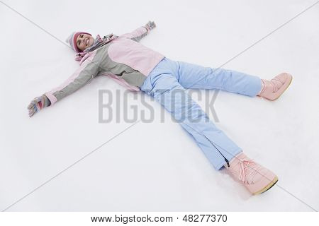 Elevated portrait view of a smiling young woman lying on snow