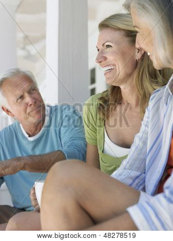 Mature man with two middle aged women sitting on verandah