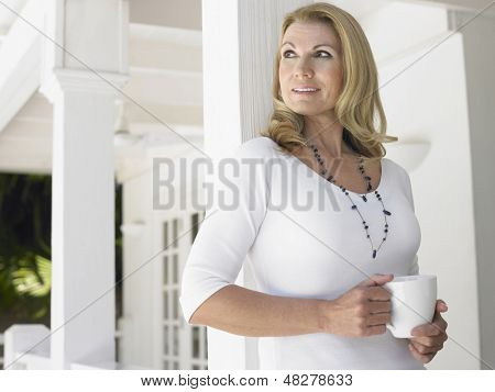Middle aged woman with coffee cup standing on verandah and looking away