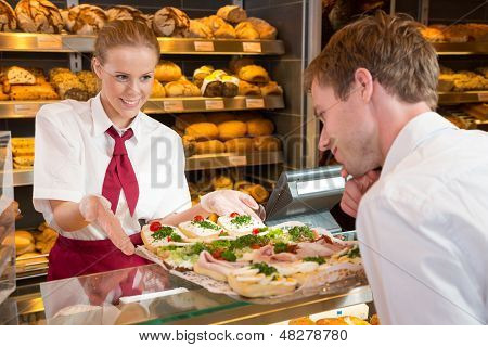 Saleswoman In Bakery Presenting Sandwiches To Customer