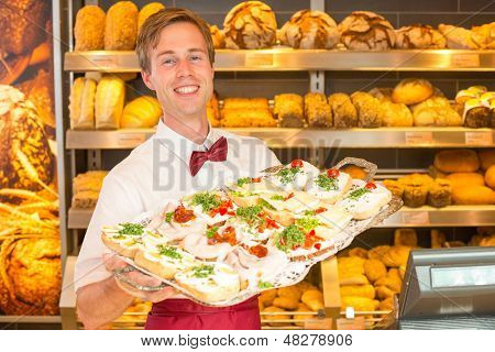 Shopkeeper In Baker's Shop With Tray Of Sandwiches