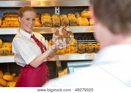 Saleswoman In Bakery Presenting Bread To Customer